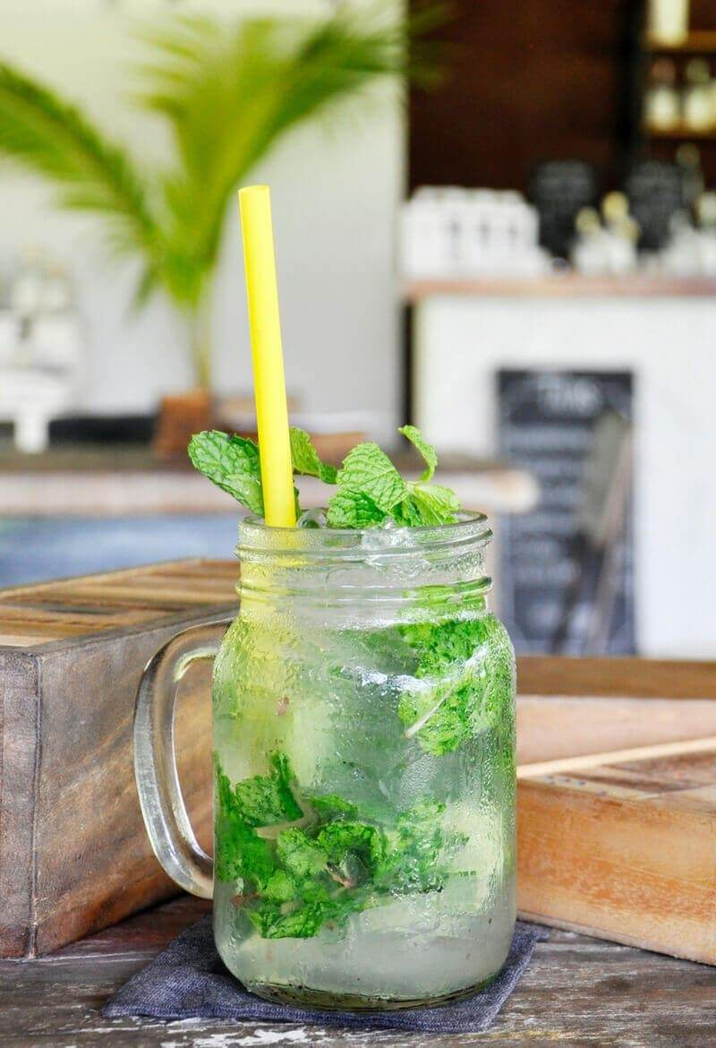 A mojito in a mason jar on a wood table