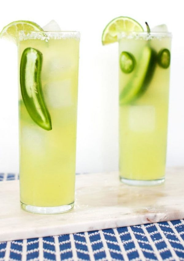 Two cocktails with jalapenos on a marble tray on a blue tablecloth.
