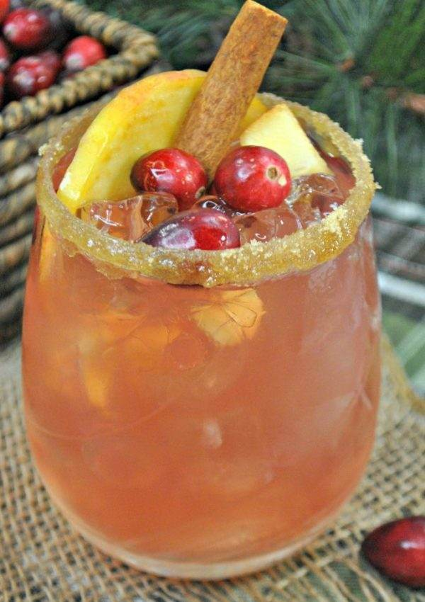 Bourbon cocktail garnished with cranberries and a cinnamon stick.