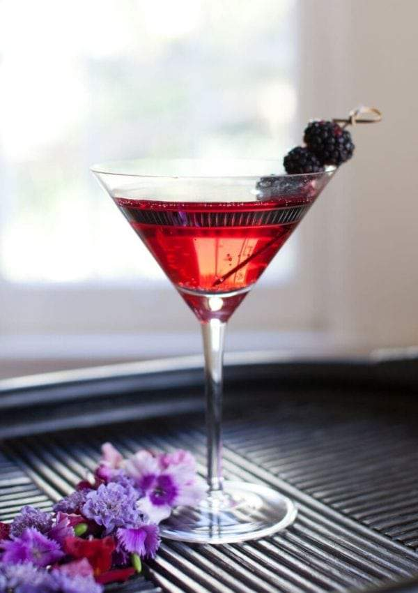 Black Raspberry Martini with Limoncello Cocktail Recipe. Served garnished with fresh blackberries in a martini glass on a bamboo tray.