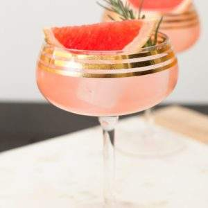 Cocktail Recipe for Elderflower Grapefruit Sparkling Martini. Served in a gold rimmed champagne coupe and garnished with a grapefruit wedge and rosemary sprig.