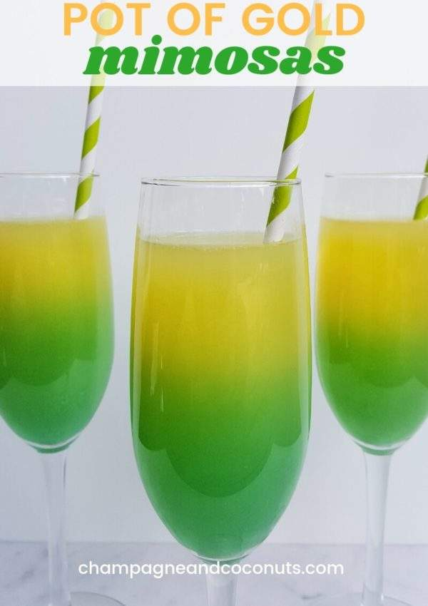 Pot of Gold Mimosas Recipe made with champagne, blue curacao, orange juice and vodka. The yellow and green cocktail is served in a champagne flute with a paper straw.