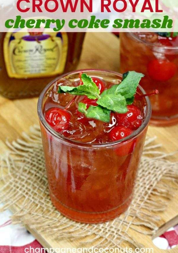 Cola and Whisky beverage with cherries on a burlap coaster with a bottle of Crown Royal in the background.