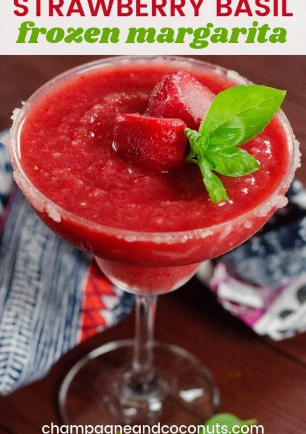 A frozen strawberry margarita garnished with fresh basil with a printed napkin on a cherry wood table.