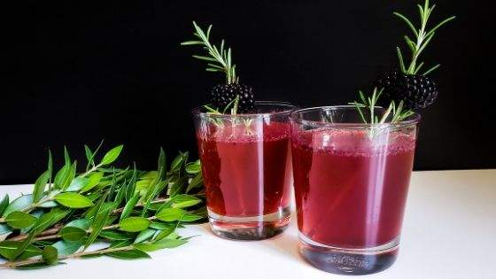 Two blackberry fireball whiskey fizz cocktails on a white table garnished with fresh rosemary and blackberries.