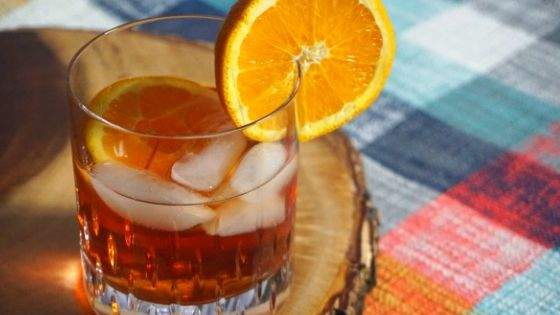 Blueberry Whiskey drink with orange wheel on a wood slice and plaid placemat