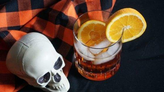 Blueberry Whiskey Corpse Reviver drink with fake skull and orange buffalo plaid napkin