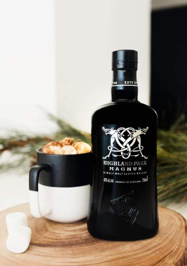 A mug of hot chocolate with a bottle of Highland Park Magnus Scotch Whiskey