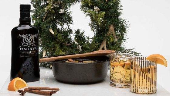 a bottle of whiskey with a dutch oven and glasses filled with homemade glogg with a Christmas wreath