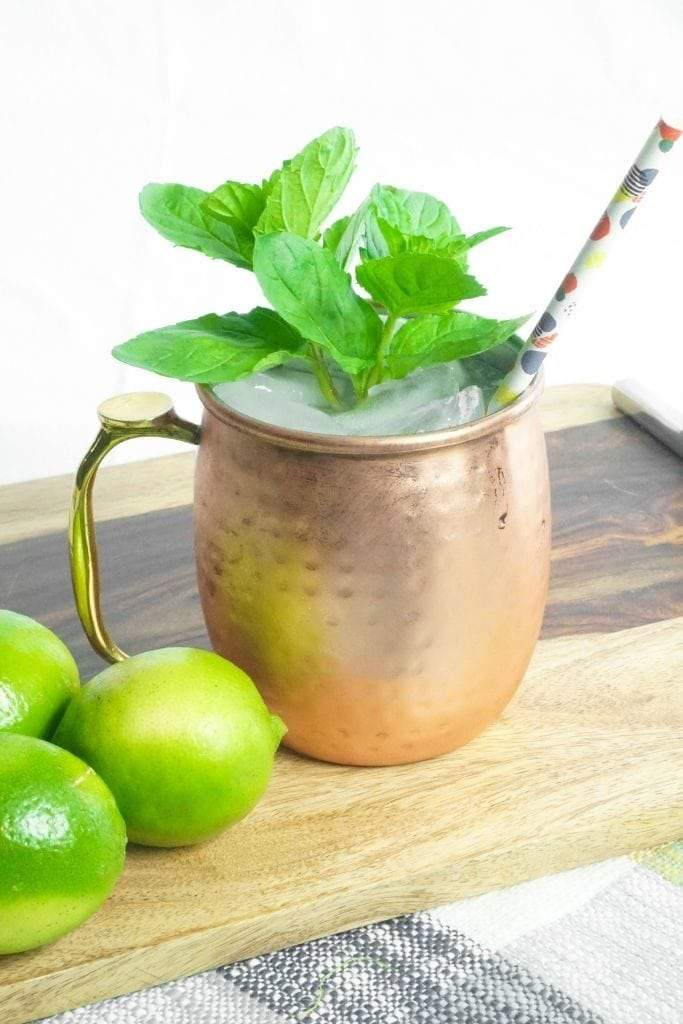 A copper mule mug garnished with mint next to some limes.