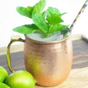 A cocktail in a copper mug garnished with mint and a straw next to some limes.