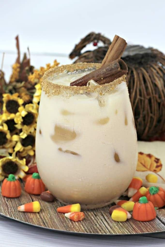 A creamy cocktail served on the rocks on a platter with Halloween candy.