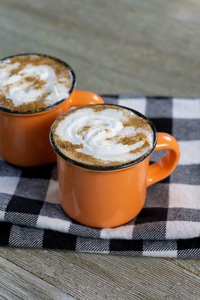 Two orange mugs filled with espresso topped with whipped cream and cinnamon