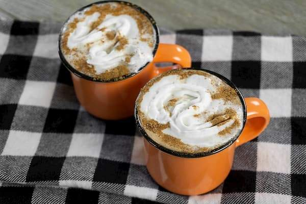 Orange mugs on buffalo plaid napkins filled with espresso topped with whipped cream and cinnamon