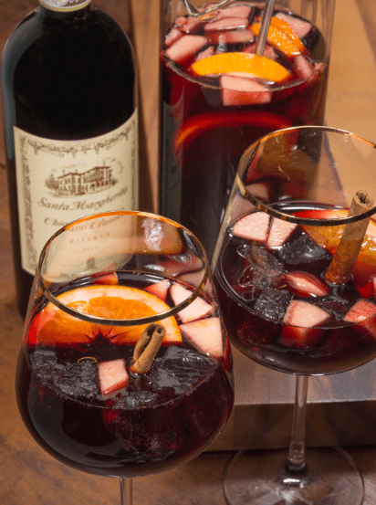 Two wine glasses filled with holiday red sangria with a bottle of chianti.