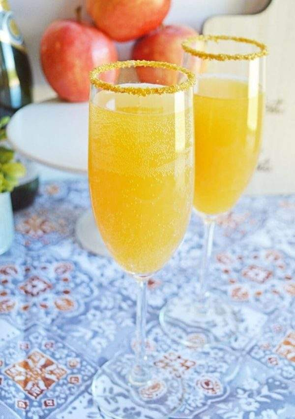 Two champagne flutes filled with apple cider mimosas on a table with a stack of apples in the background.