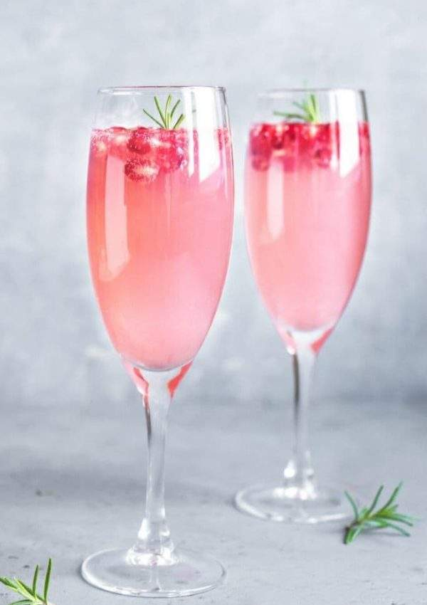 Two champagne flutes filled with French Rose Champagne Punch garnished with rosemary and pomegranate seeds on a gray backdrop.