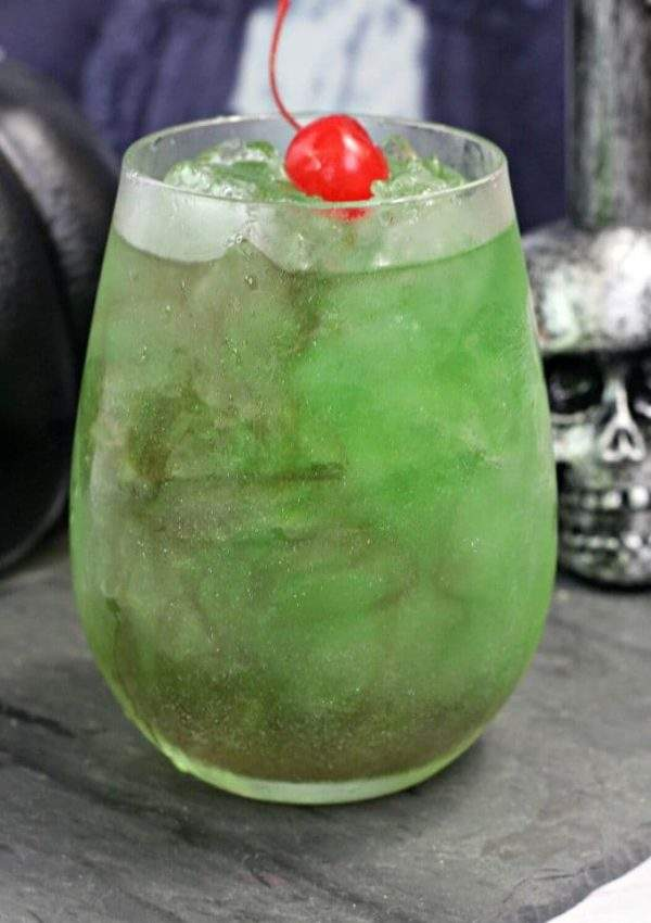 A shimmery green cocktail inspired by Harry Potter, the Death Eater's draught sits next to a silver skull.