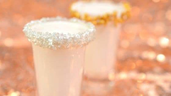 Two shot glasses filled with Spiced Rum Milk Shots with silver and gold sprinkles on a rose gold sparkly background.