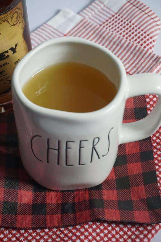 A Rae Dunn mug that says Cheers filled with Mulled Apple Cider Wassail next to a bottle of whiskey sitting on a buffalo plaid napkin.