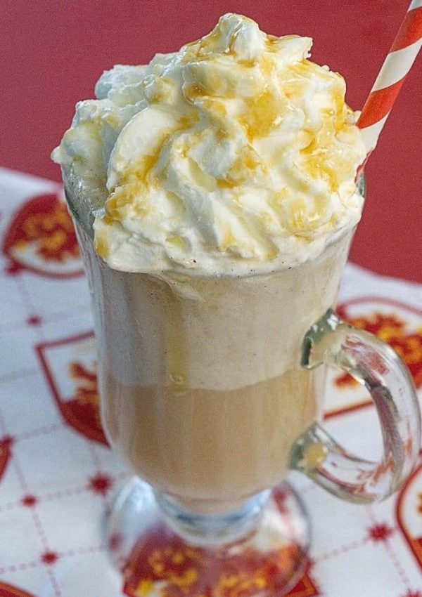 A tall clear mug filled with a butterbeer float topped with whipped cream on a Gryffindor placemat.