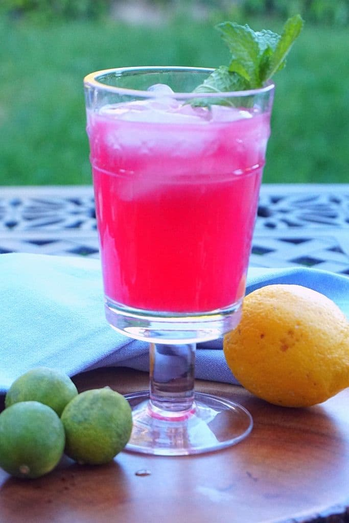 A blueberry cocktail rests on a wood platter with limes and a lemon on an outdoor table.