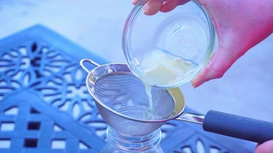 In process: pouring lime juice through a mesh strainer into a jar.