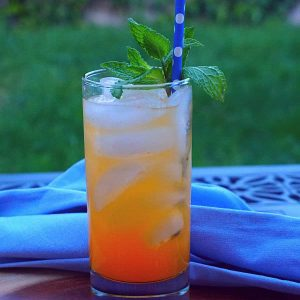 An outdoor table with an orange drink sitting on it garnished with mint and a blue straw.