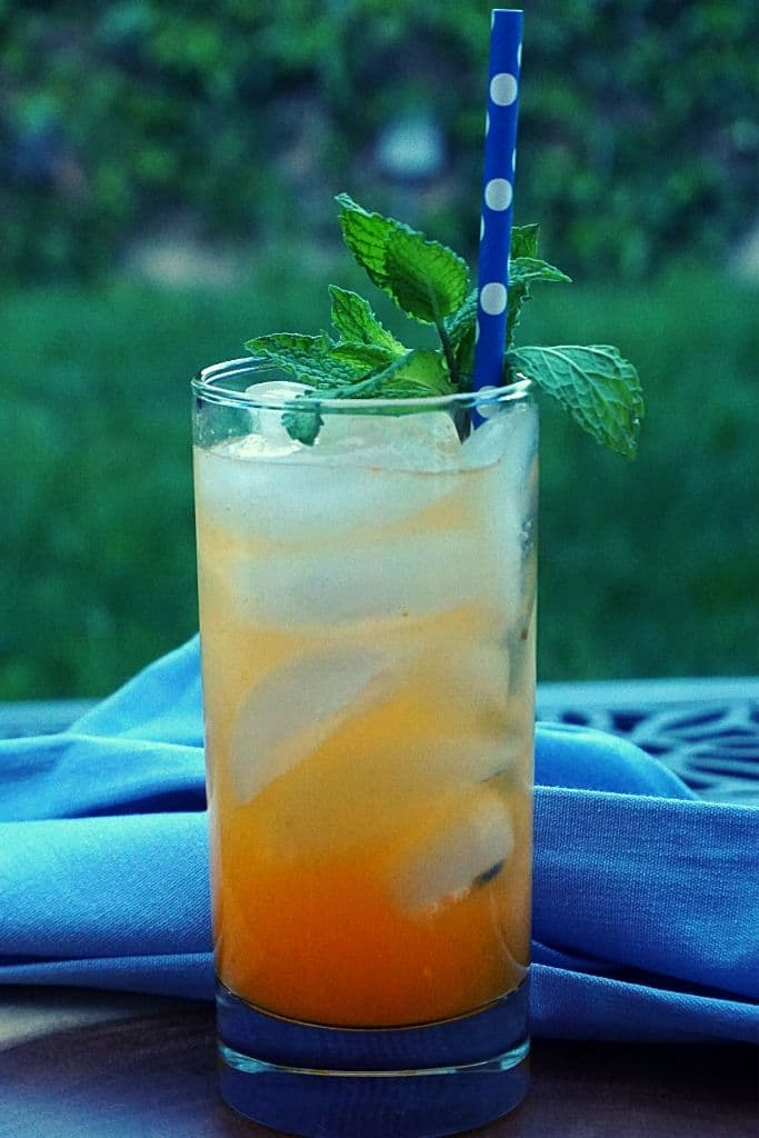 An orange beverage garnished with mint with a blue towel on an outdoor table.