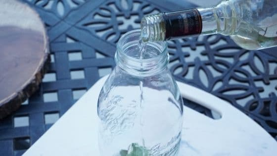 Process shot of pouring rum into a jar on an outdoor table.