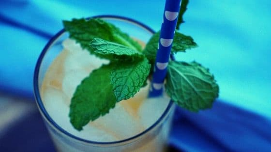A sprig of fresh mint rests next to a blue polka dot straw in a cocktail.