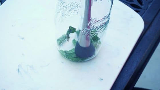 Muddling fresh mint in a glass jar on a table.