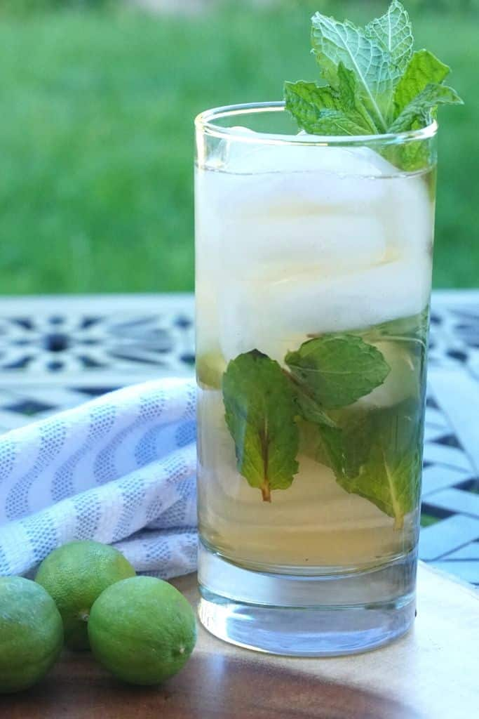 A cocktail with mint leaves rests on a wood plate on a patio table.