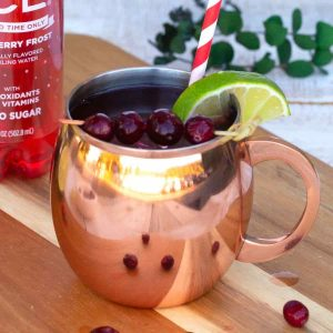 Cranberries garnish a cranberry ginger beer Moscow mule cup next to a bottle of Sparkling Ice.