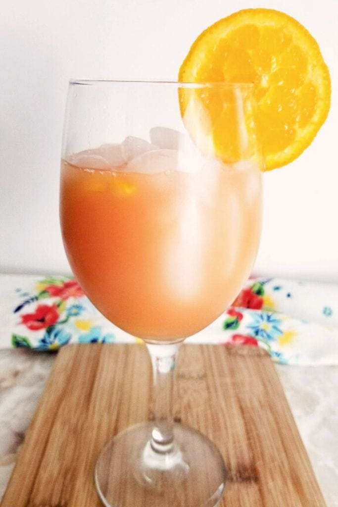 A close up of a wine glass filled with punch, garnished with an orange slice on a wood board.