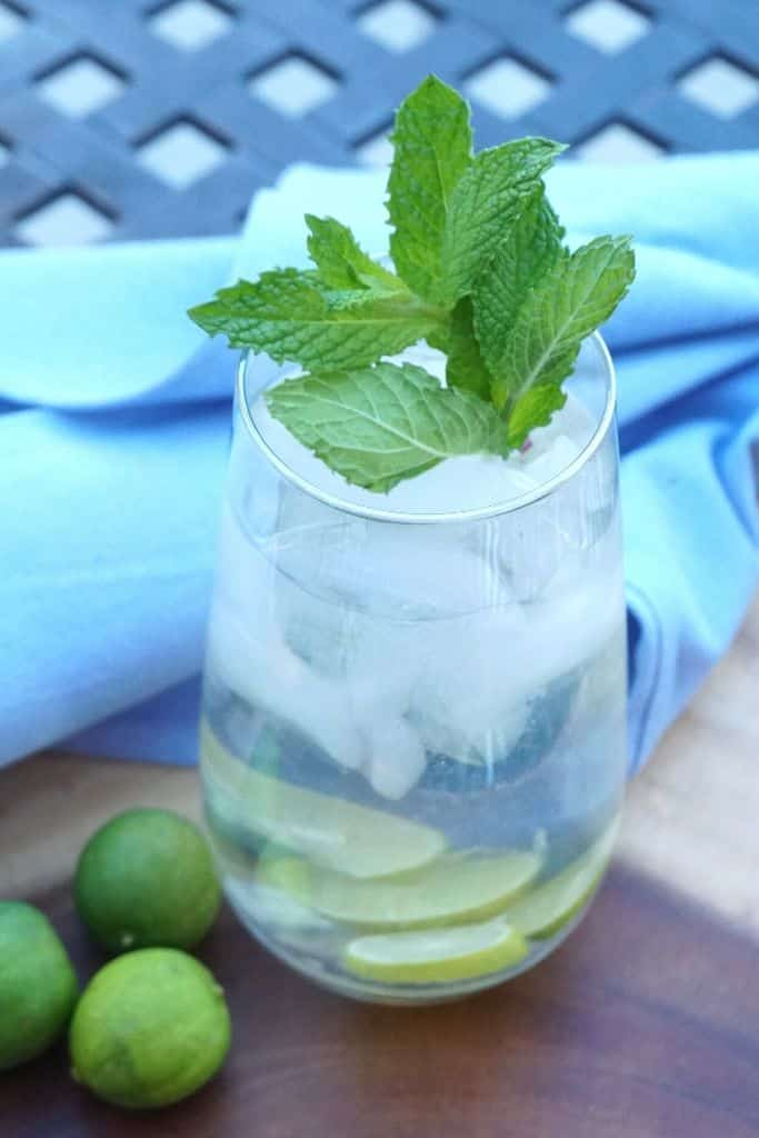 A cucumber and lime cocktail garnished with fresh mint on a platter with a wood napkin.