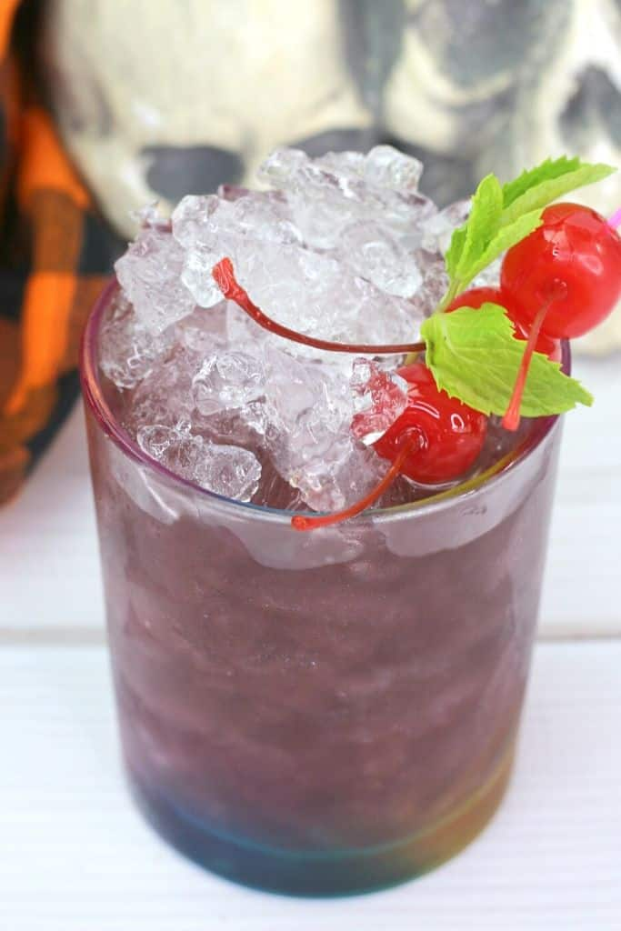 A purple cocktail with an ice dome garnished with cherries and mint.