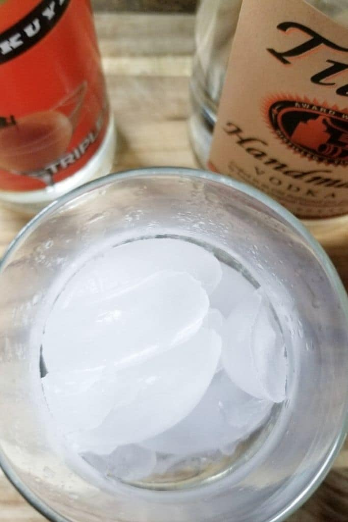 Ingredients to make Orange Cranberry Punch - a glass of ice, a bottle of triple sec and Tito's Vodka.