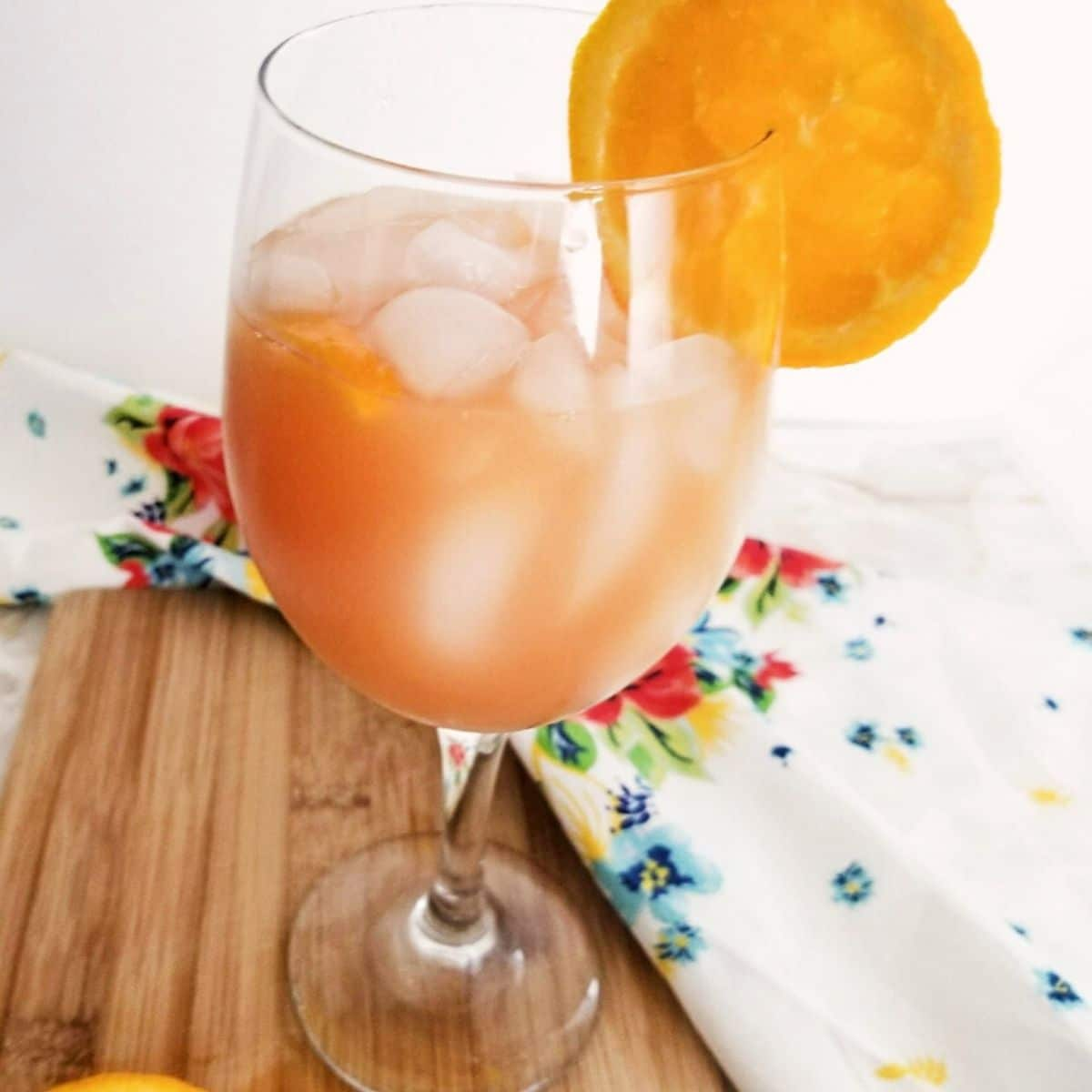 A wine glass filled with punch garnished with an orange slice.