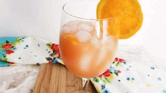 A glass or orange punch on a wood cutting board with an orange wheel for garnish.