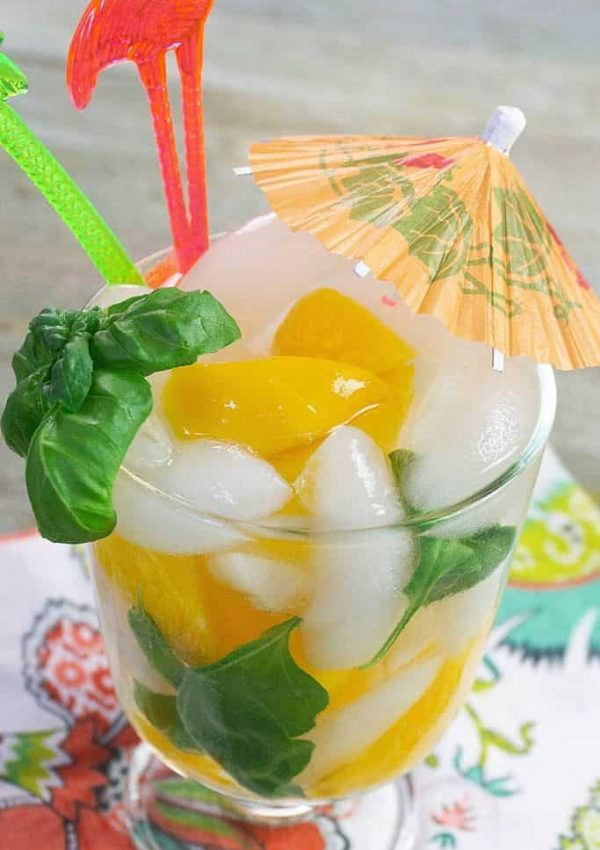 An orange cocktail umbrella stuck in a drink made with peaches and fresh basil.
