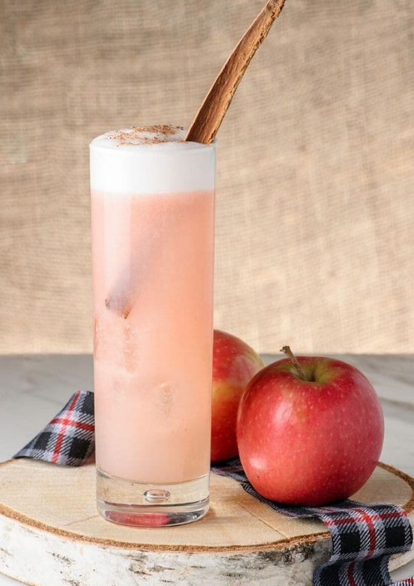 A pink cocktail rests on a wood charger next to an apple with a plaid napkin.