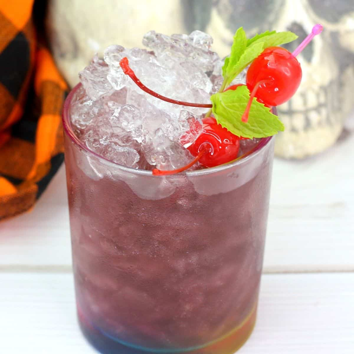 A purple cocktail with silver shimmer garnished with cherries and mint next to a Halloween skull.