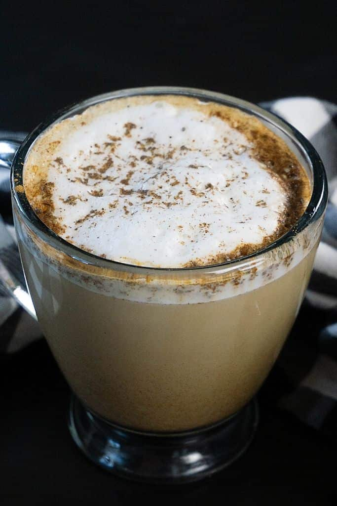 A latte sprinkled with cinnamon and cardamom spices on a black table.
