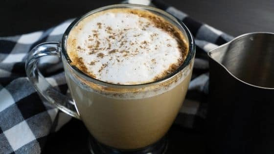 A coffee mug with a latte topped with frothed milk, cinnamon, and cardamom.